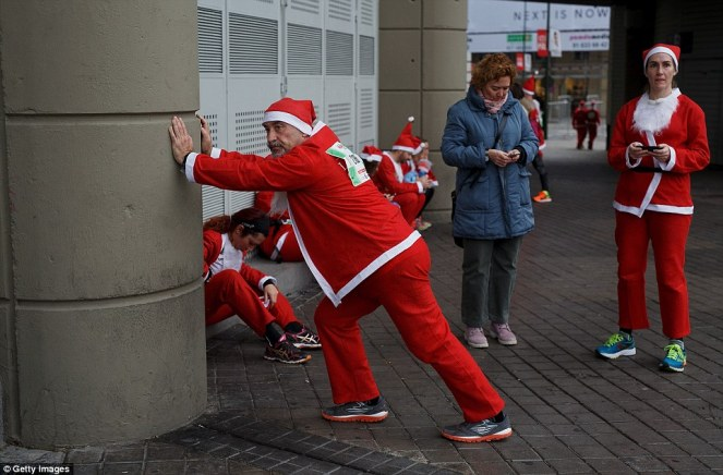 2F4E0B1E00000578-3357499-Getting_ready_A_participant_stretches_in_his_Santa_suit_after_ta-a-1_1449961668229